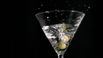 Olives in super slow motion falling in a martini