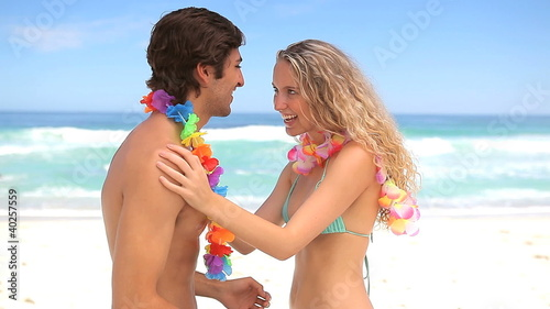 Couple putting flower necklace to each other