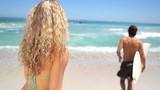Woman kisses her boyfriends who's going to surf