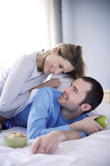 Young couple in bed, looking at each other, smiling