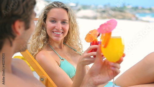 Couple sitting on deck chairs toasting