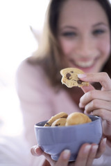 Woman holding bowl full of cookies, close-up