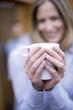 Woman holding mug, smiling, close-up