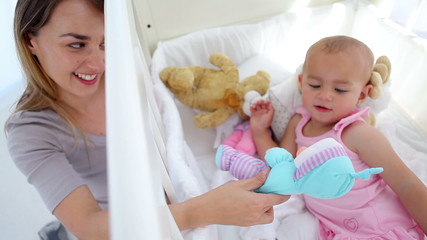 Woman playing dolls with her baby