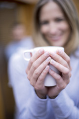 Woman holding mug, smiling, close-up