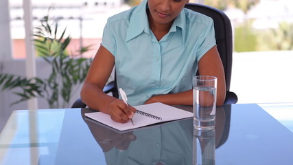 Well-dressed woman writing on a notebook