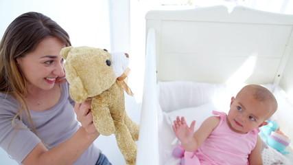 Baby girl kissing her teddy bear