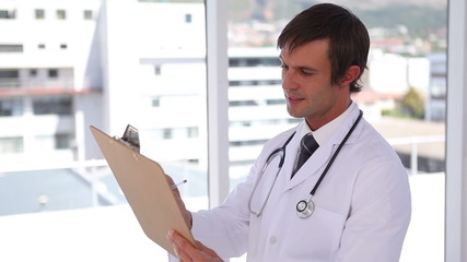 Doctor writing on a clipboard while standing