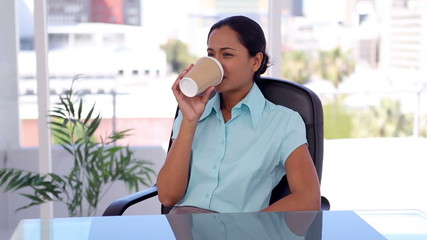 Well-dressed woman drinking a coffee