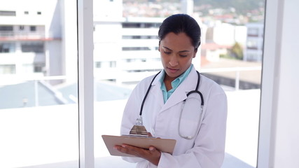 Female doctor writing on a file