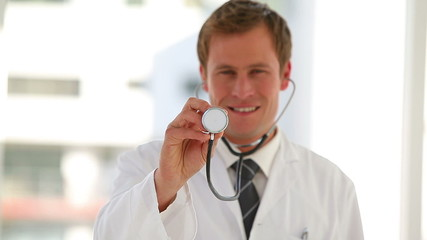 Doctor holding up his stethoscope while smiling