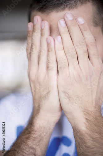 Man covering face with hands, close-up