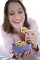 Young woman holding cookies, close-up