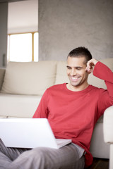 Young man looking at laptop, smiling