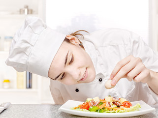 young chef decorating delicious salad in kitchen
