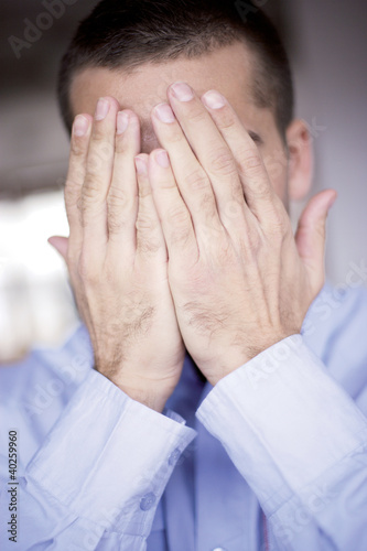 Young man covering face with hands, close-up
