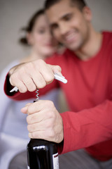 Young man opening wine bottle