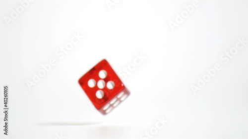 Red single die falling in super slow motion