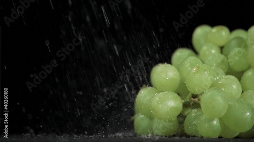 Raindrops in super slow motion falling on grapes