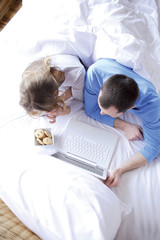 Young couple in bed with laptop and cookies