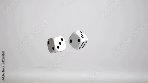 Hand in super slow motion throwing a pair of dice