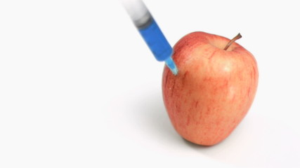Syringe in super slow motion falling on an apple
