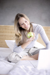 Young woman in bed with green apple and laptop, smiling