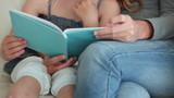 Mother helping her daughter read a book