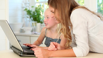 Mother and daughter typing on a laptop