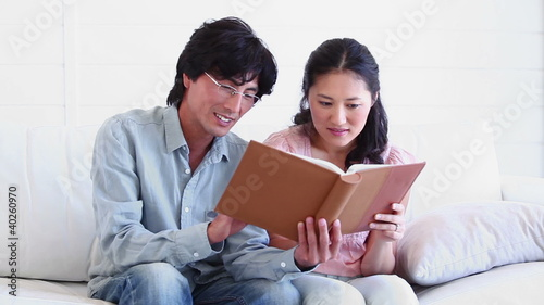 Man and a woman reading a book together