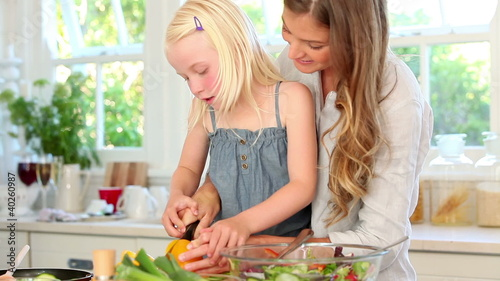 Mother and daughter cutting a pepper together