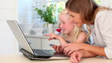 Mother and daughter laughing as they use a laptop