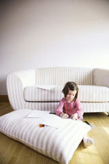 Girl sitting by sofa with color pencils and paper