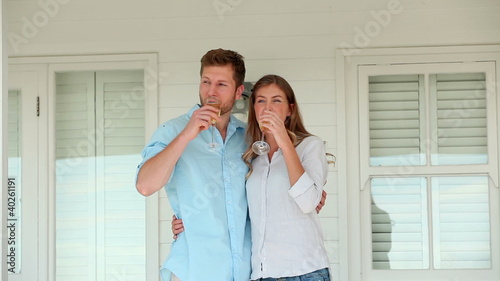 Man and a woman clinking glasses of champagne before holding each other