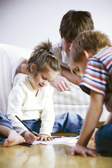 Father with children looking at drawing, smiling