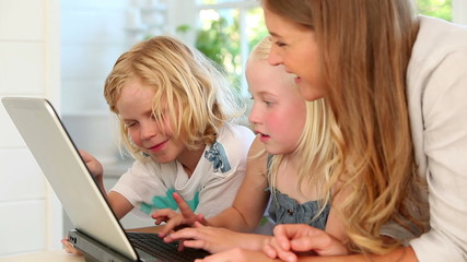 Mother using a laptop with her children