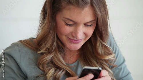 Woman writing a text message while smiling
