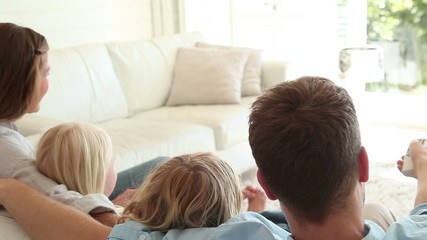 Family sitting together while watching television