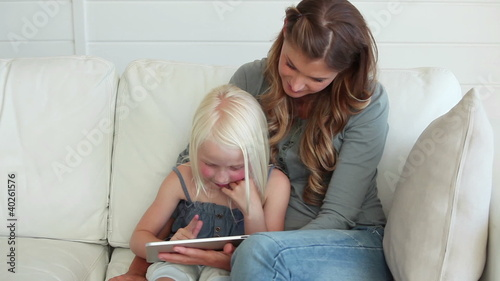 Mother using a tablet computer with her daughter