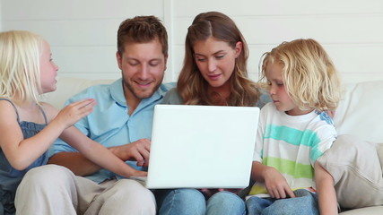 Family sitting together while using a laptop