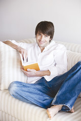 Young man with book sitting on sofa, smiling, portrait