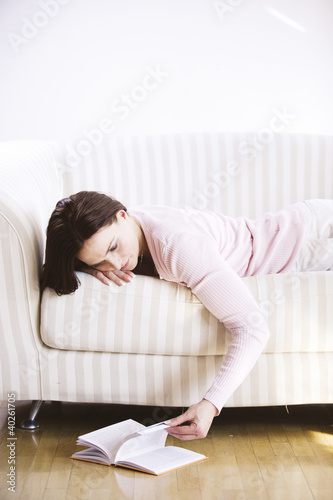 Young woman looking at book, lying on sofa