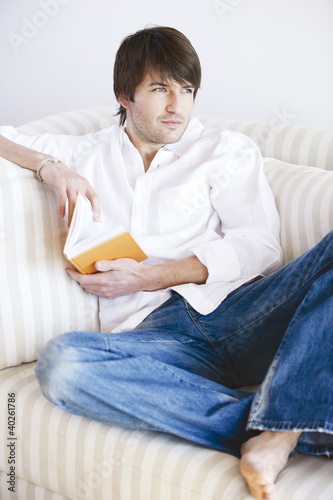Young man with book sitting on sofa, looking away