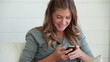 Woman smiling while writing a text message