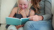 Girl laughing as she is reading a book with her mother