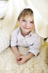 Boy lying on carpet, smiling, portrait