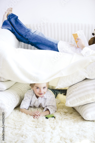 Boy lying on carpet while father reading book on bed