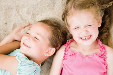Sisters relaxing on sand, overhead view