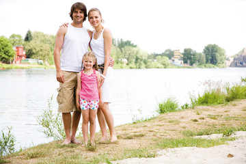 Daughter with parents standing by lake, portrait