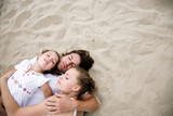 Parents with daughter lying on sand
